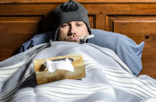 A man sick in bed with a thermometer in his mouth